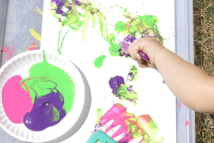 toddler using spoon to paint