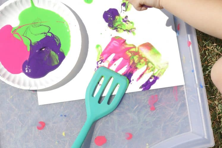 toddler using spoon to paint on cardstock
