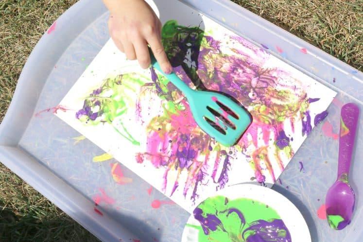 kindergartner painting with spatula