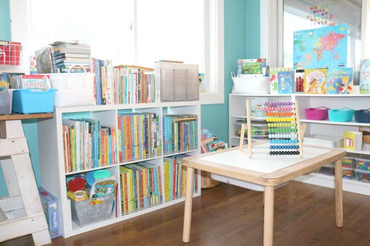wooden sensory table in front of cube shelves filled with books