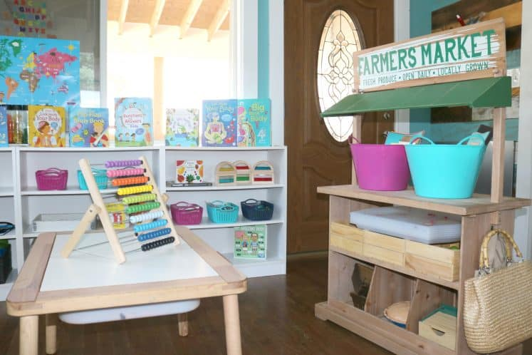 preschool homeschool room with Farmer's Market dramatic play and shelves filled with learning toys