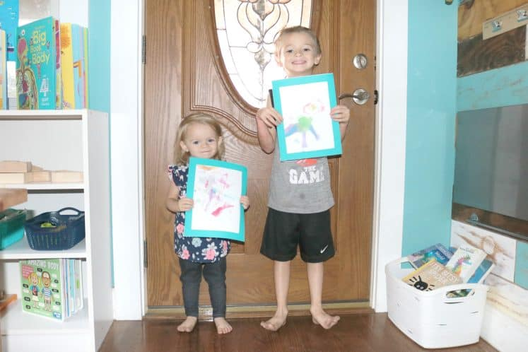 two children holding All About Me Theme self-portrait art