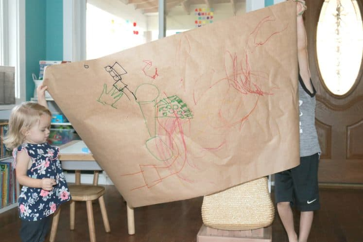 two children holding large kraft paper art project