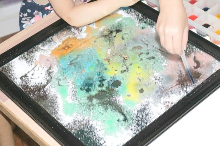 preschooler dripping colored water on salt