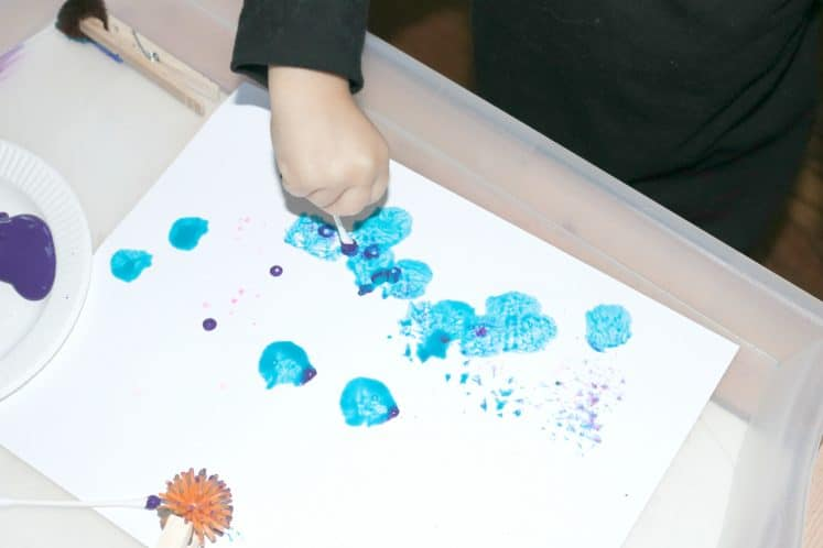 preschooler painting with a cotton swab