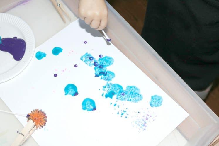preschooler using a cotton swab to paint dots