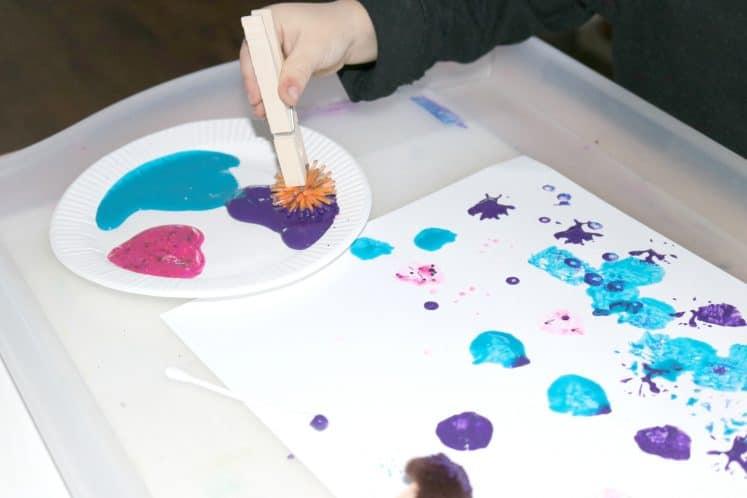 preschooler painting with pokey ball