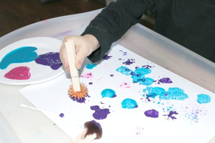 preschooler using pokey ball to paint dots
