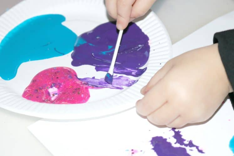 preschooler using paint and cotton swab to make dots