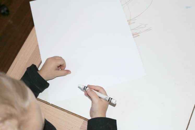 preschooler drawing with white crayon