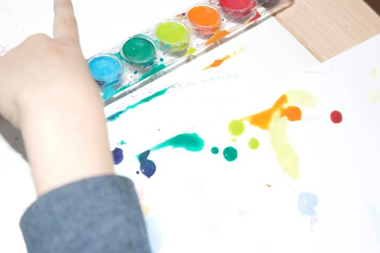 child using watercolors to create wax resist painting