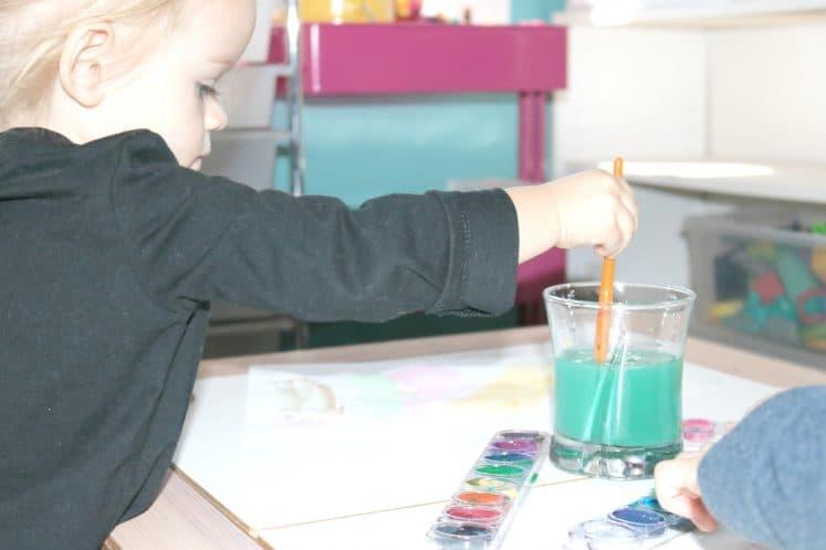 preschooler dipping brush into water