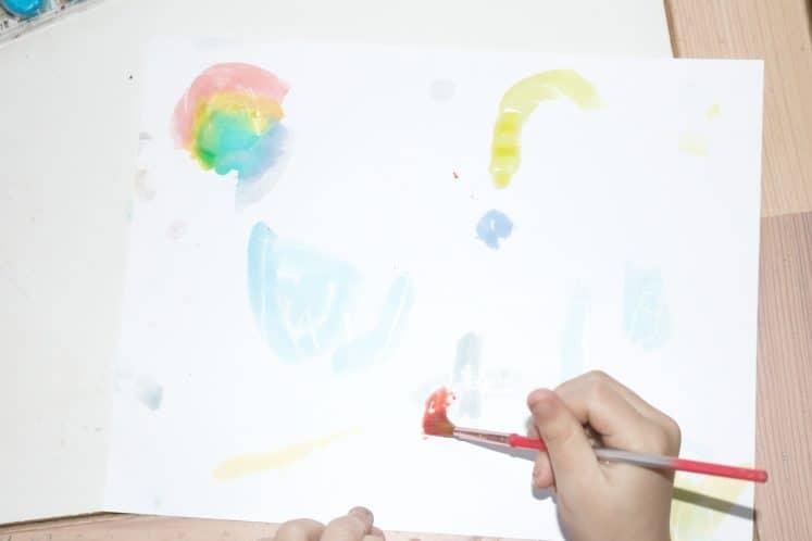child adding watercolor to resist artwork
