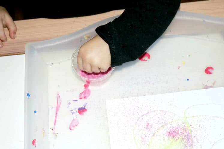 preschooler sprinkling sand on cardstock