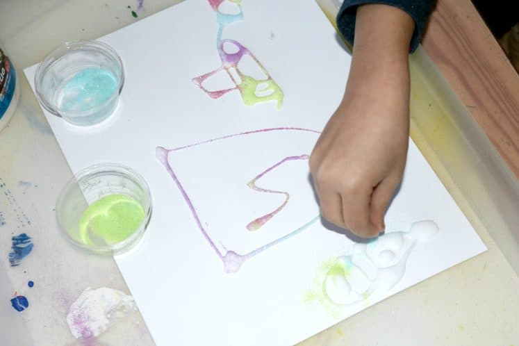 child sprinkling sand on process art