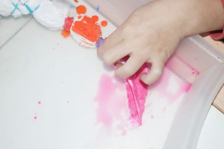 child dripping dye on tie-dye art