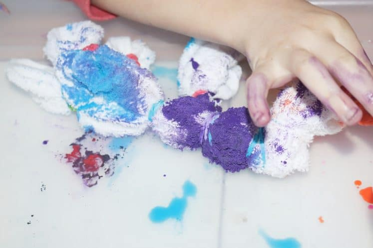 child using dropper to tie-dye fabric