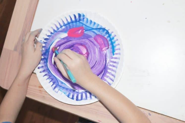 child making tornado art using paint