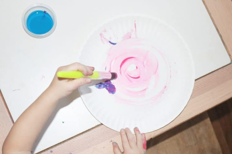 preschooler making swirls with paint on a paper plate