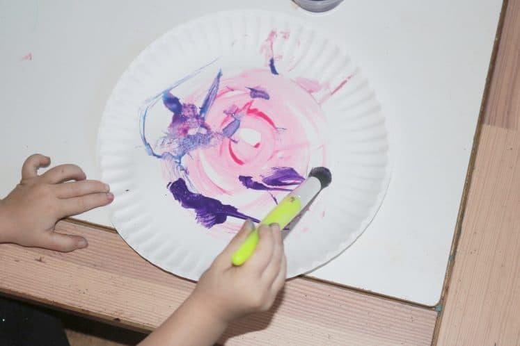 preschooler making swirls with paint