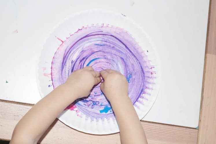 child finger painting swirls on paper plate