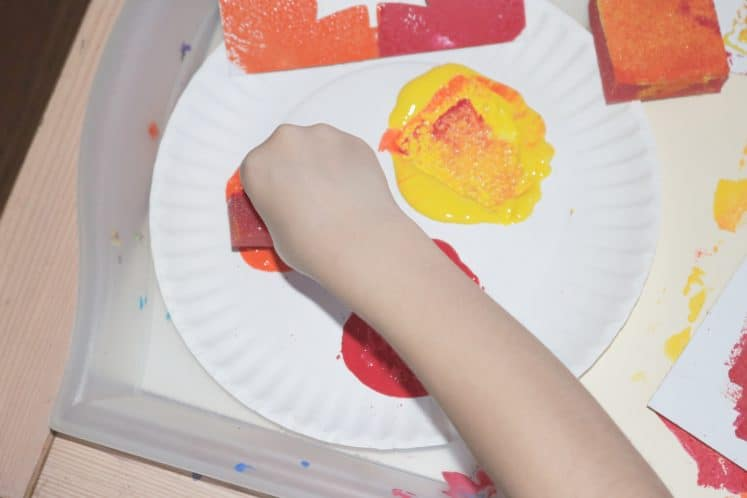 child dipping sponge in paint to make fall process art