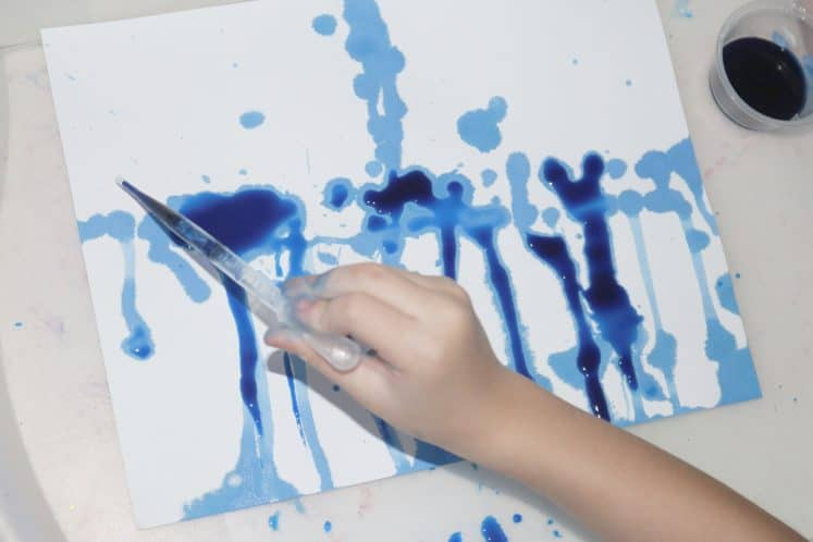 child making spring process art using paint and cardstock