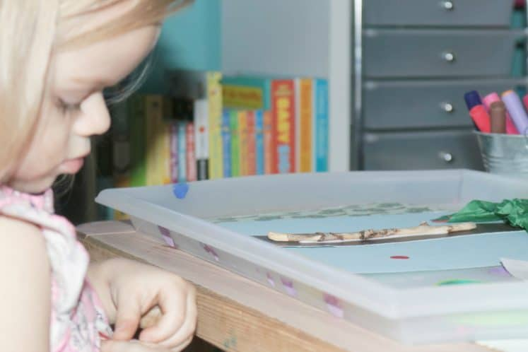 preschooler removing red dot stickers from sheet