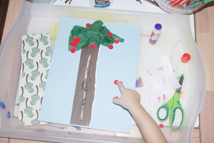 preschooler adding red dot stickers to cherry tree process art