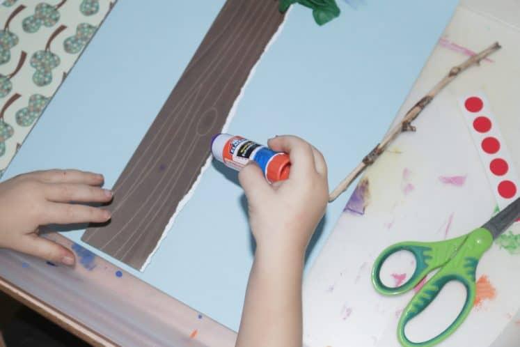 preschooler gluing paper tree trunk to background paper