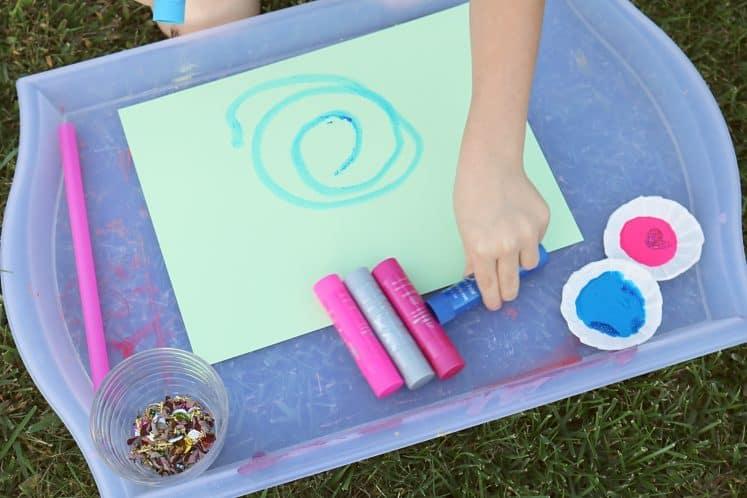 child drawing wind swirls on cardstock