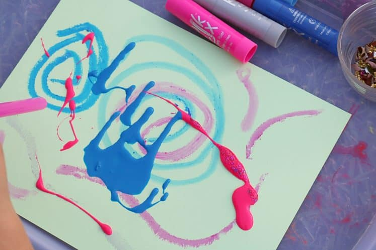 child using straw to blow paint around on cardstock