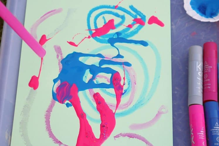 child blowing on paint to move it around cardstock