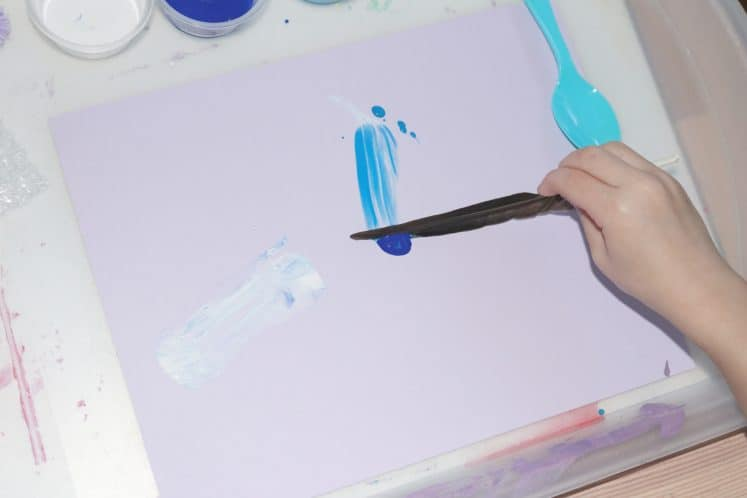 preschool painting with a feather to make winter process art