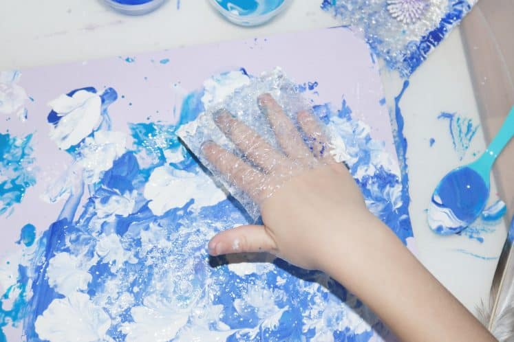 child using bubble wrap to create winter process art