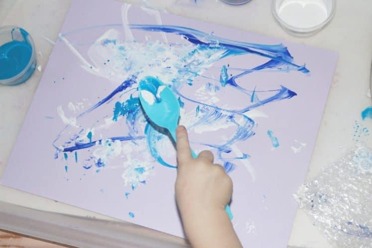 preschooler using spoon to create winter process art
