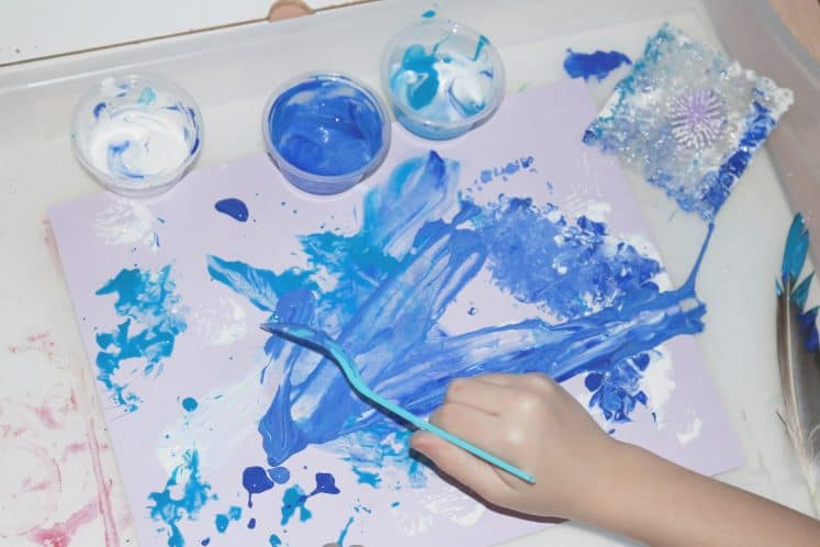 child using spoon to create snowstorm process art