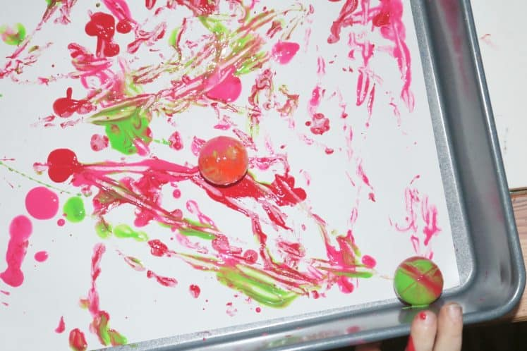 child dropping paint-covered rubber ball into tray