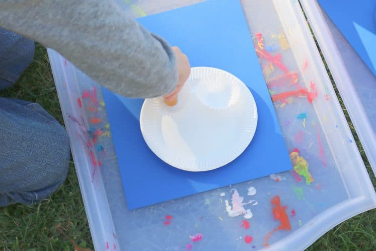 child painting paper plate to make lotus flower process art