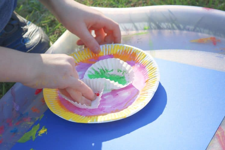 child pressing painted cupcake liner onto paper plate