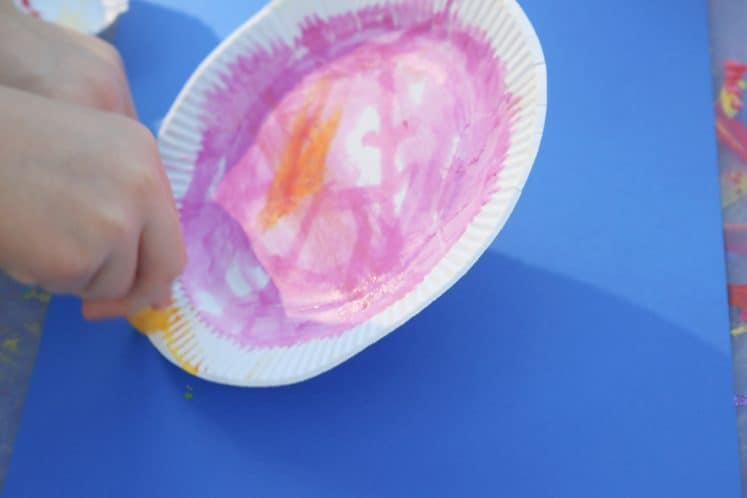 child painting paper plate with paint sticks
