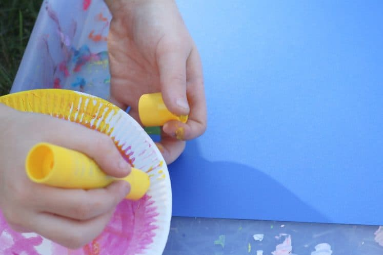 child painting edge of paper plate yellow