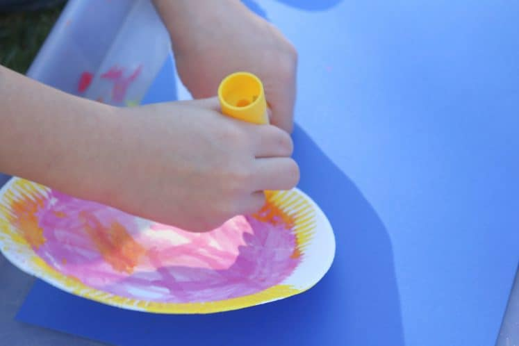 child painting edge of paper plate