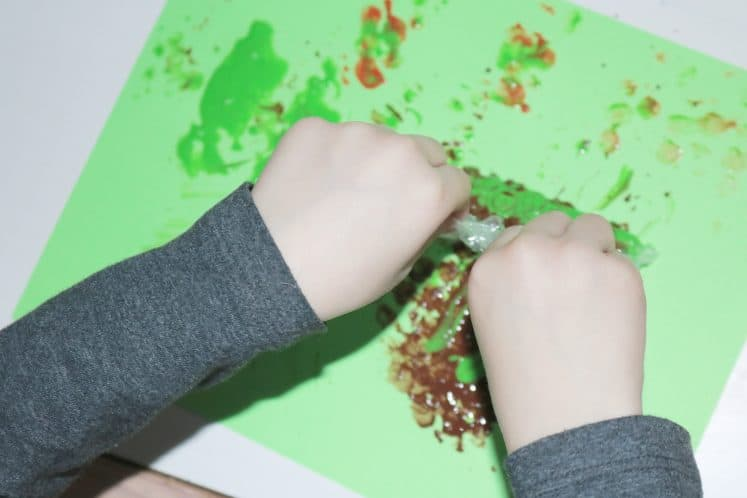 child stamping on cardstock with bubble wrap