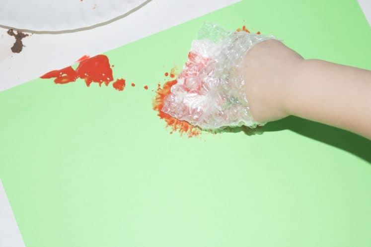 preschooler dabbing paint on cardstock using bubble wrap