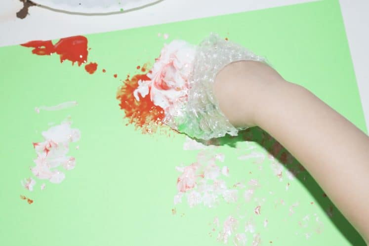 preschoolers dabbing paint onto cardstock using bubble wrap