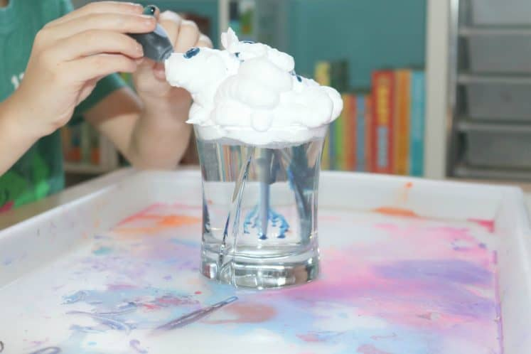 child dripping food coloring into glass filled with water and shaving cream
