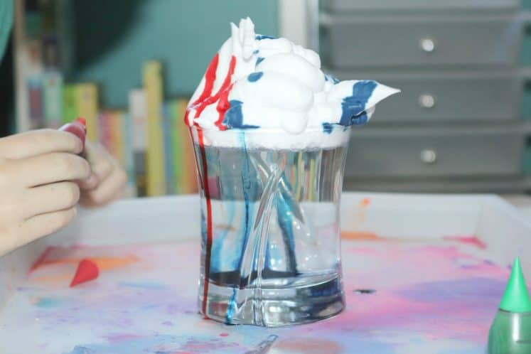 red and blue food coloring being dripped on shaving cream