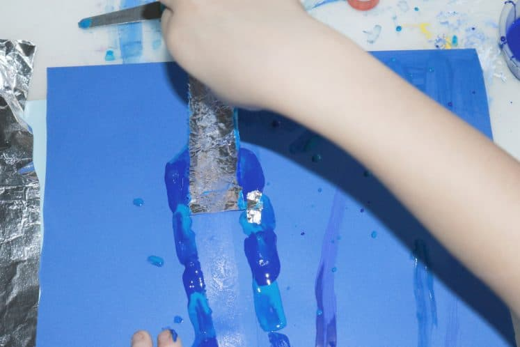 child removing aluminum foil from cardstock while creating icicle process art