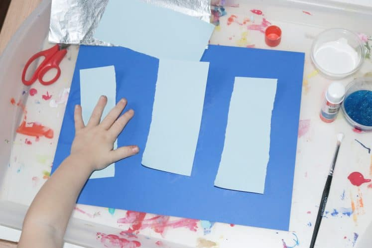 preschooler gluing cardstock onto icicle painting for kids